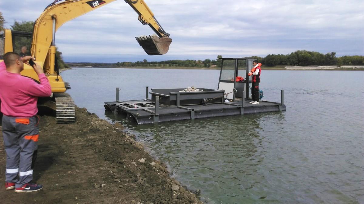 plastični ponton na reci sa utovarenim materijalom